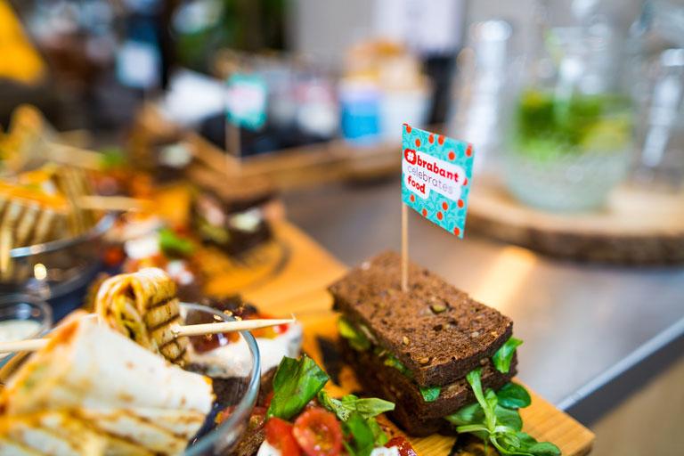 allerlei lekkere hapjes met close-up op een prikkertje met de tekst Brabant celebrates food