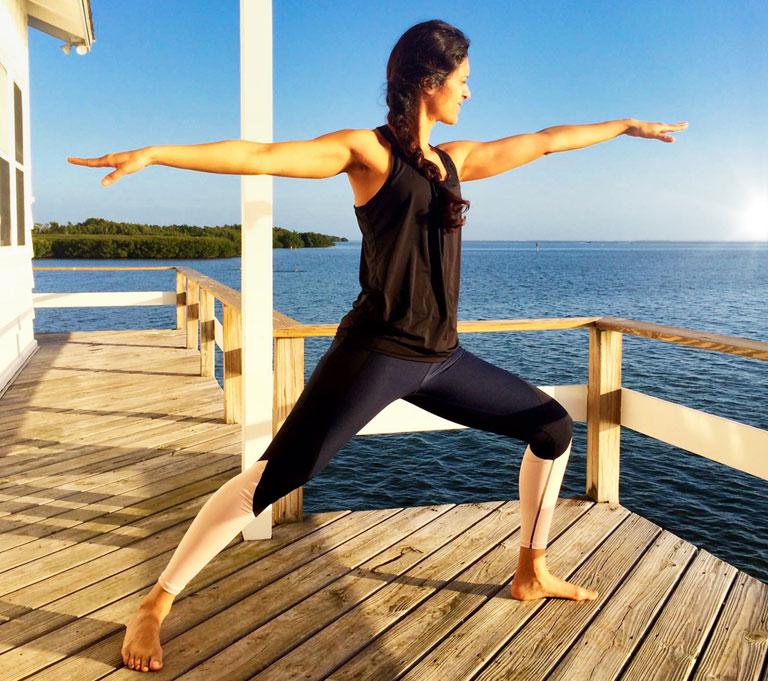 Zarina die yoga doet bij zonsopkomst in Florida
