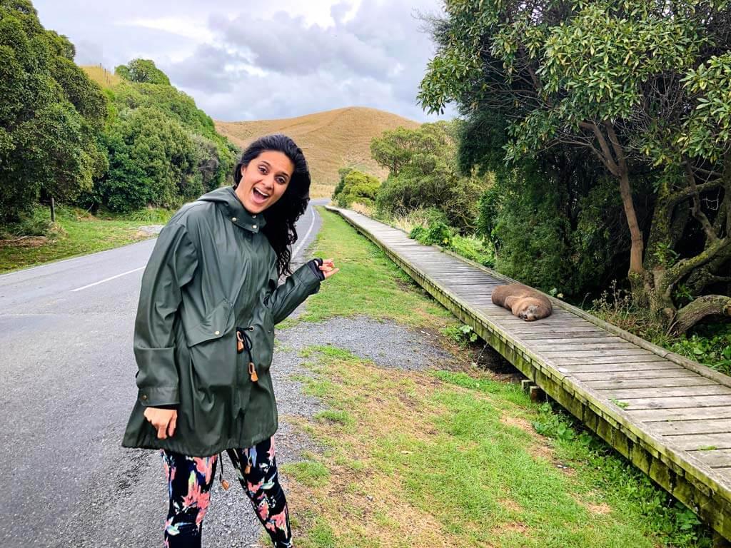 Zarina al lachend in Nieuw-Zeeland en wijzen naar een slapende zeehond