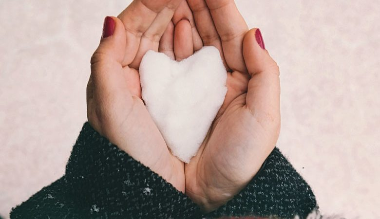 paar vrouwenhanden met daarin een hartje van sneeuw