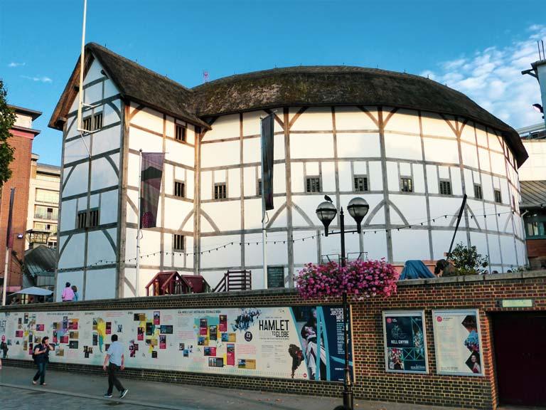 buitenkant van de ronde en witte Globe Theatre met rieten dak