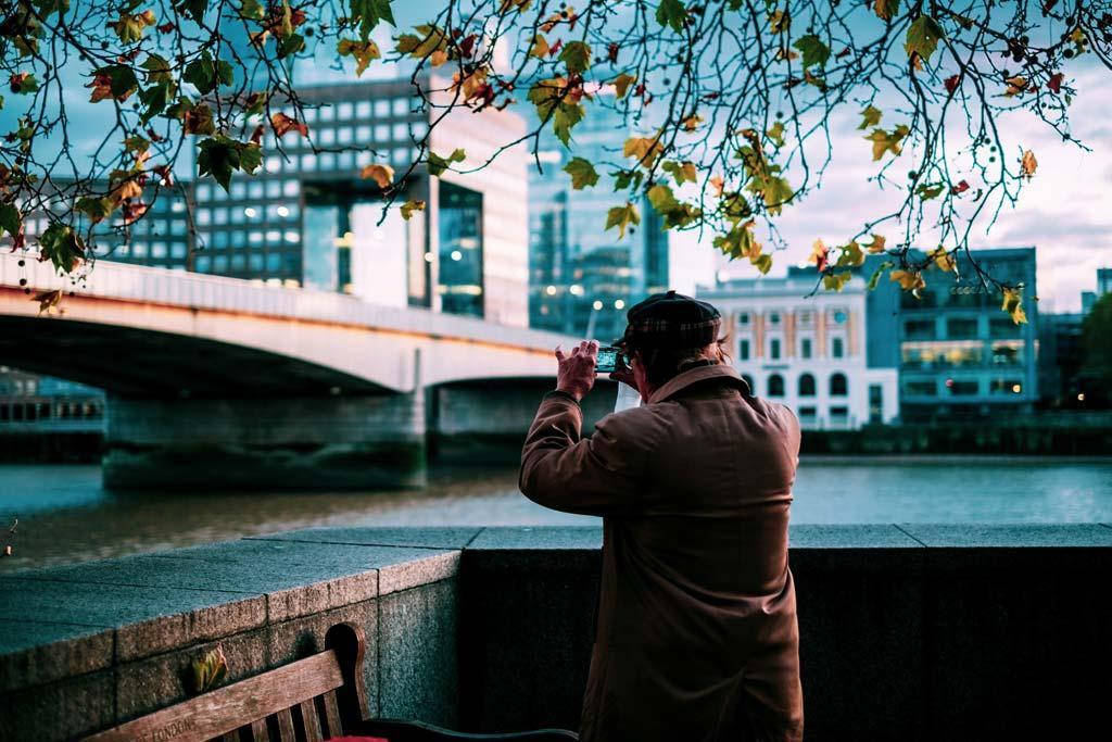 man gezien van achteren die een foto van London Bridge neemt