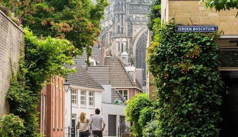 stelletje dat door een pittoresk straatje kruisend aan de straat Jeroen Boschtuin in Den Bosch loopt met in de achtergrond deel van de Sint Janskathedraal